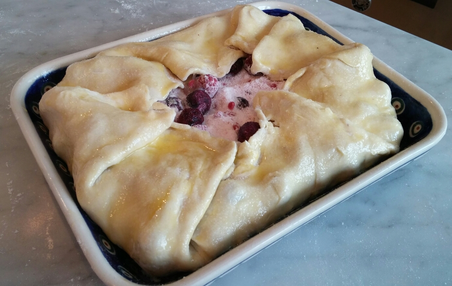 Fold the dough up and over the frozen berries, paint with egg wash, and sprinkle with granulated sugar