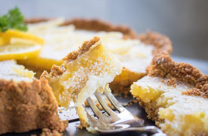 Lemon tart with pistachio cardamom crust on a fork