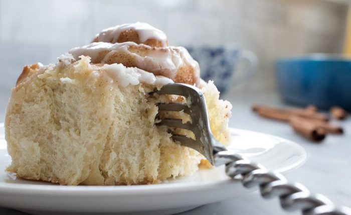 Glazed cinnamon rolls upclose with leading fork