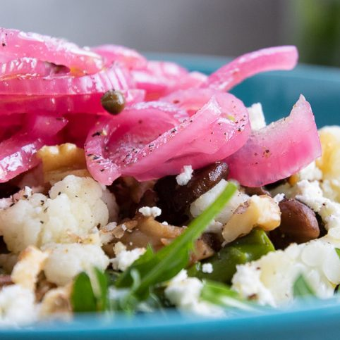 Pickled red onions on top of a salad