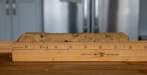 Log of chocolate chip cookie dough with a ruler so you can cut them into 1-inch slices