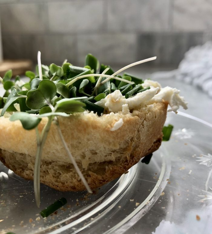 English muffin with cream cheese, garden chives, and micro greens